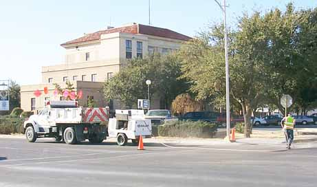 Texas Department of Transportation employees work on blowing away dust and  debris from the cracks in the road on the west side of Cedar Street.